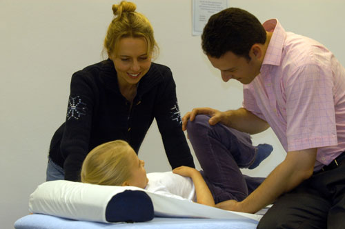 Osteopath treating a child with mum present